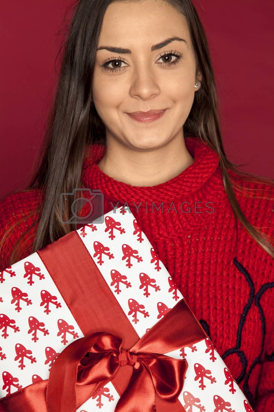 smiling young beautiful woman holding a christmas gift