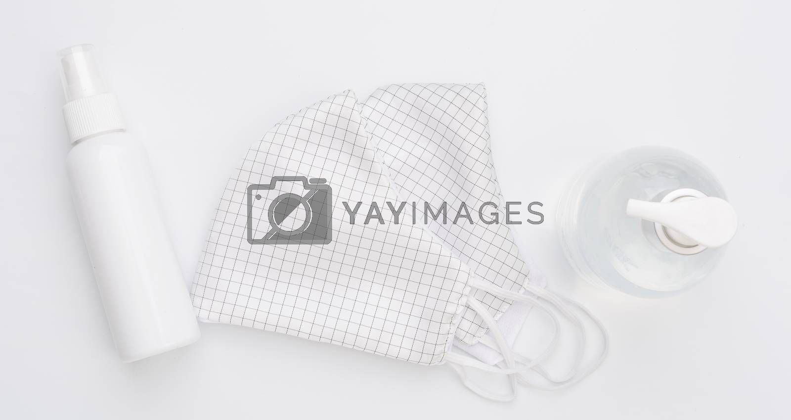 Fabric cloth mask for wearing germ protection  and gel alcohol or hand sanitizer spray bottle for washing hand  to protect from corona virus set on white background
