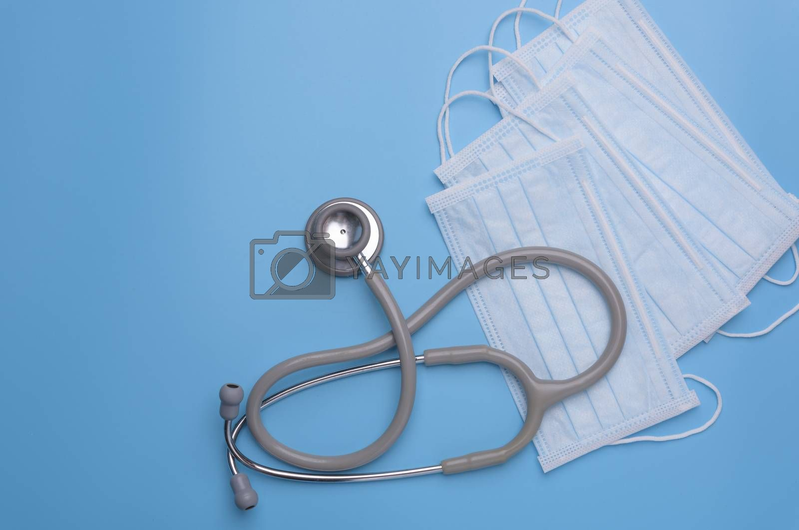 Coronavirus-Covid19,surgical ace mask protection against pollution, virus, flu  and stethoscope on blue background,top view