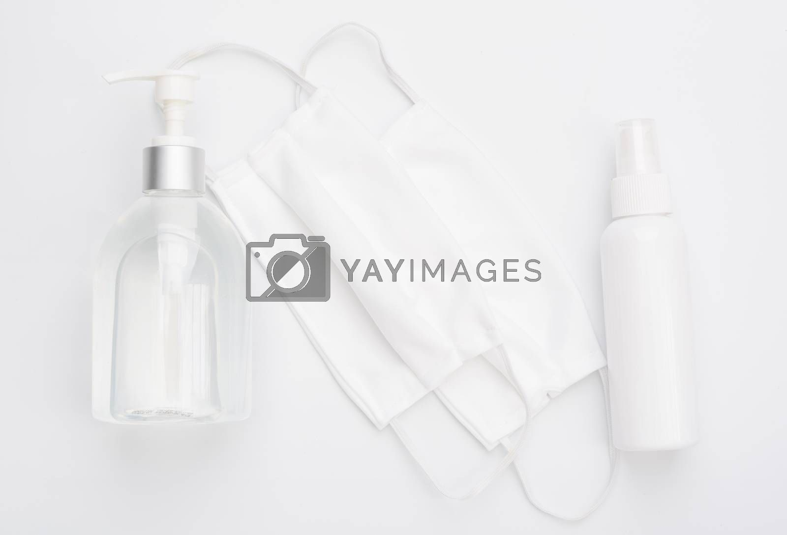 Fabric cloth mask for wearing germ protection  and gel alcohol or hand sanitizer spray bottle for washing hand  to protect from corona virus set on white background,flat lay