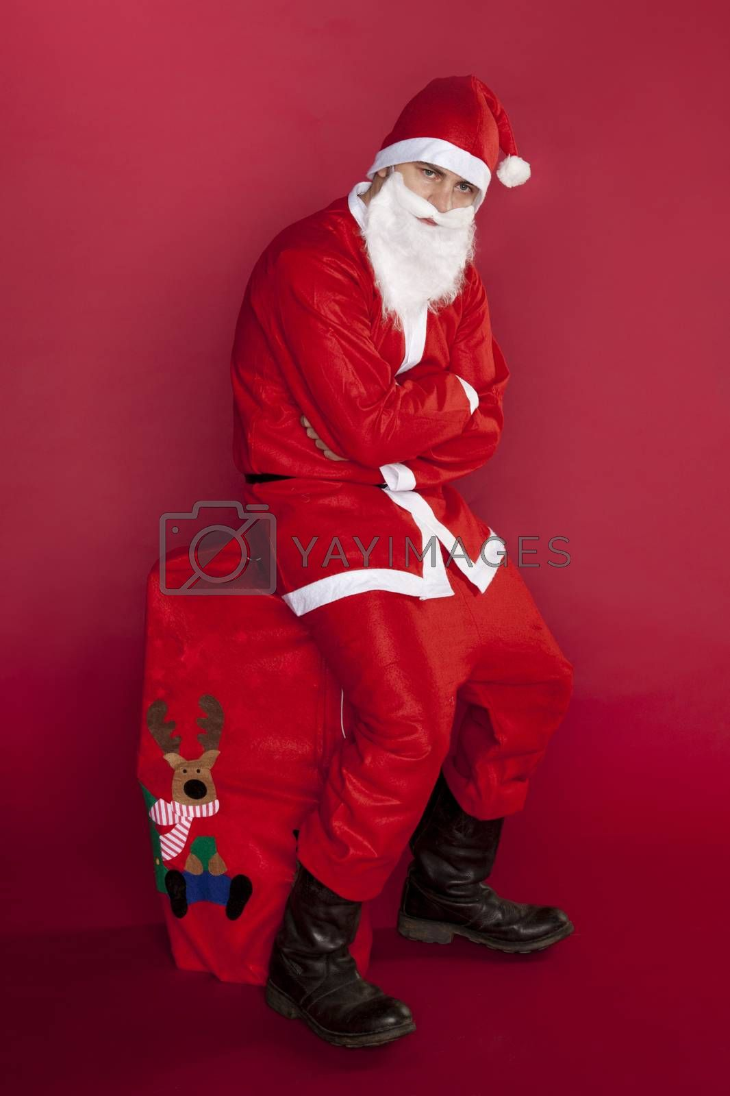Unhappy Santa Claus is sitting on a big bag stuffed with presents
