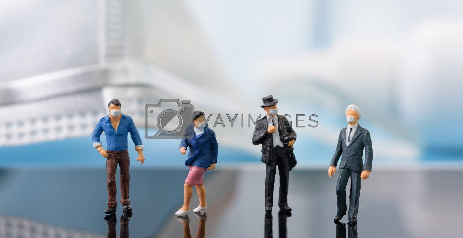 Social distancing,Miniture business people wear mask stand on mo by foto2rich