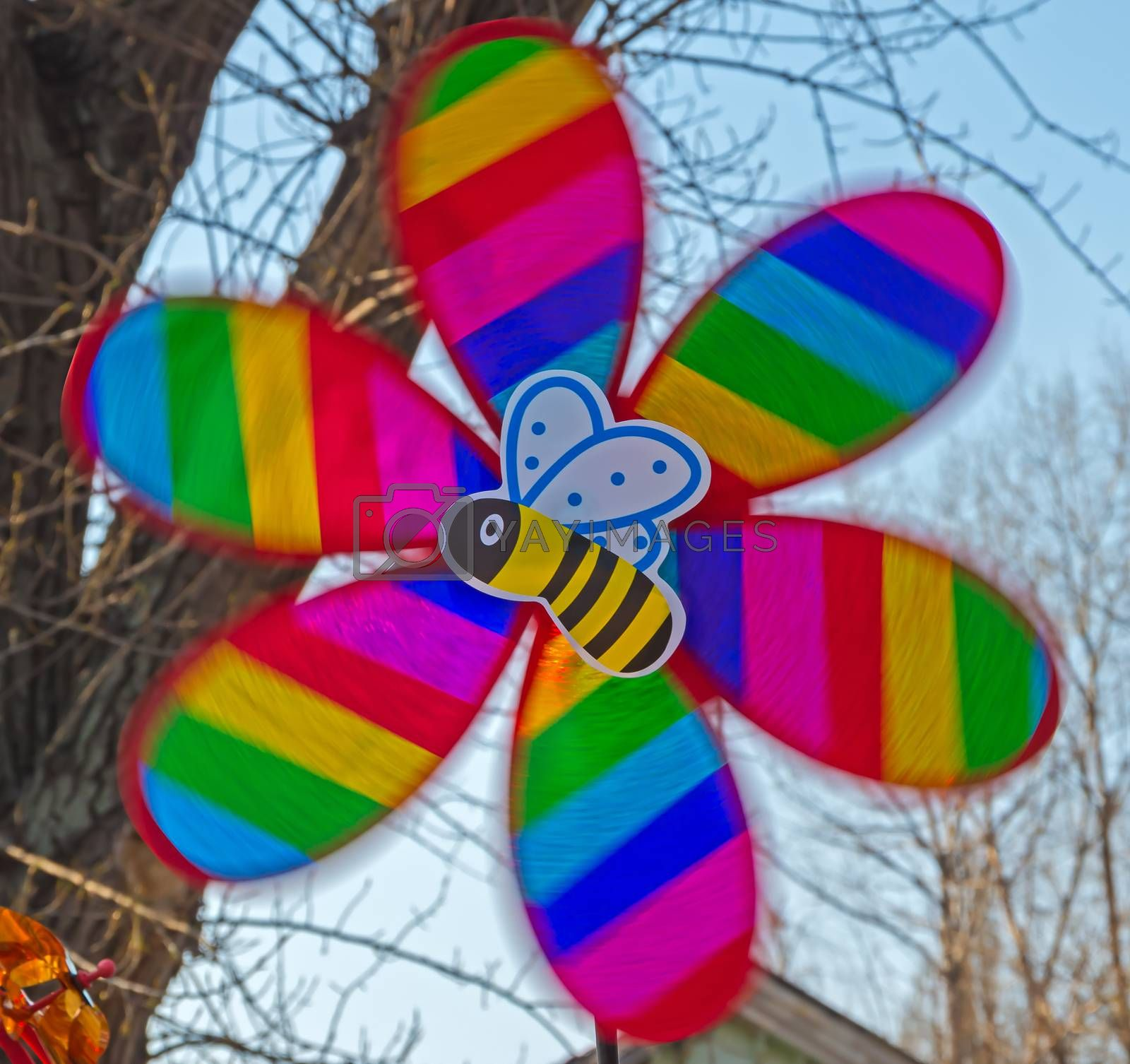 Children's multi-colored toy in the form of a propeller and bee in motion
