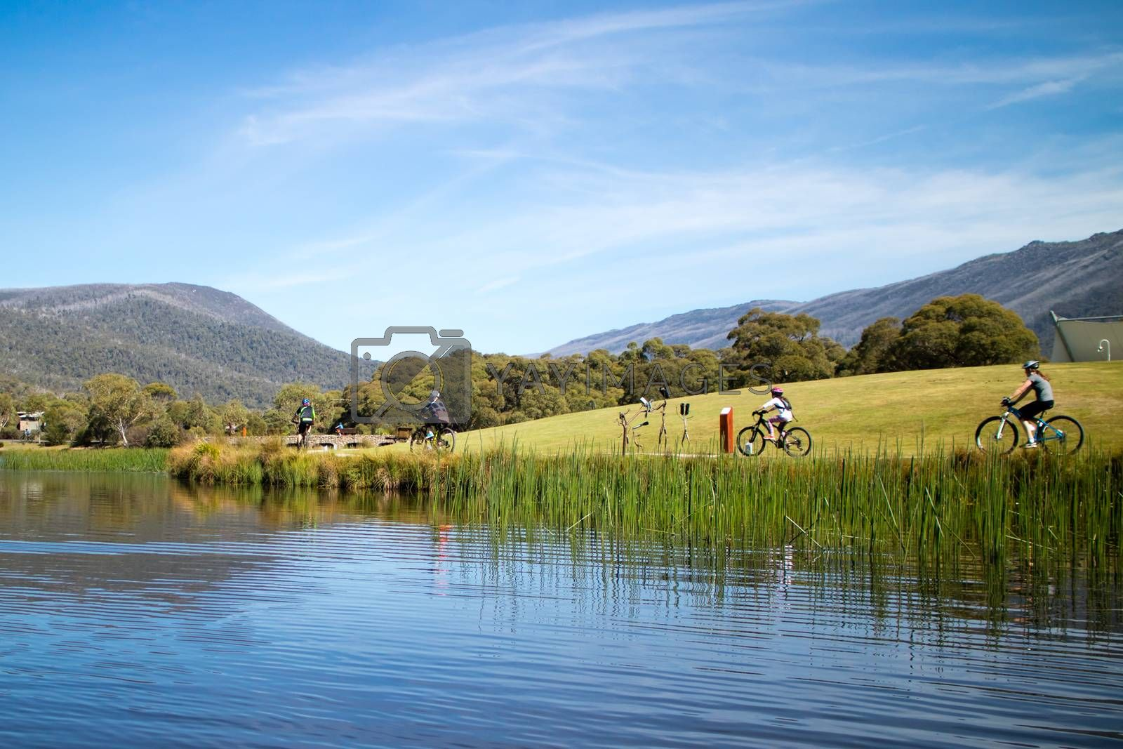 People cycling around Lake Crackenback on an autumn morning in New South Wales, Australia