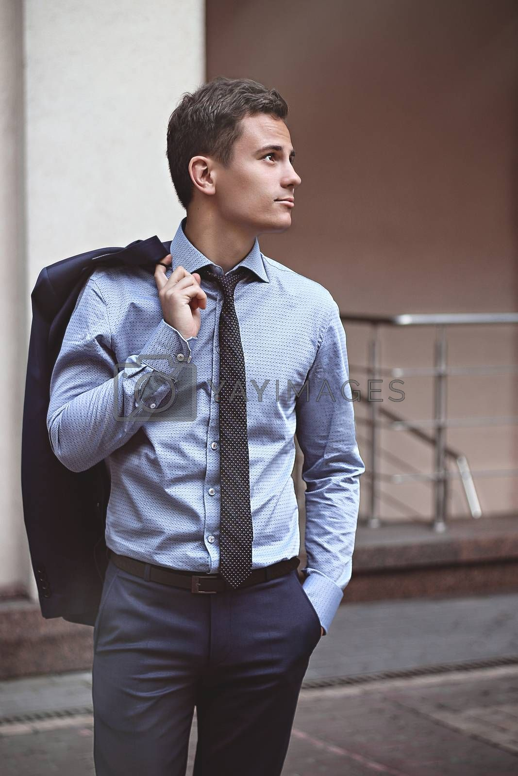 Proud businessman standing in the street looking up