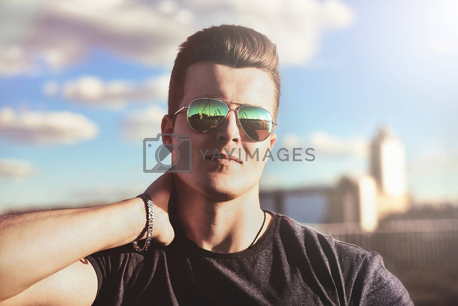 Portrait of a handsome stylish guy in sunglasses who poses outdoors