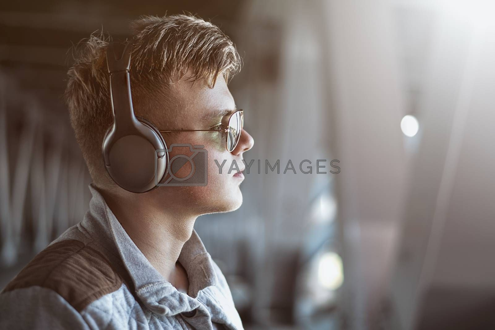 Portrait of a young stylish man listening to music with earphones . Lifestyle concept.