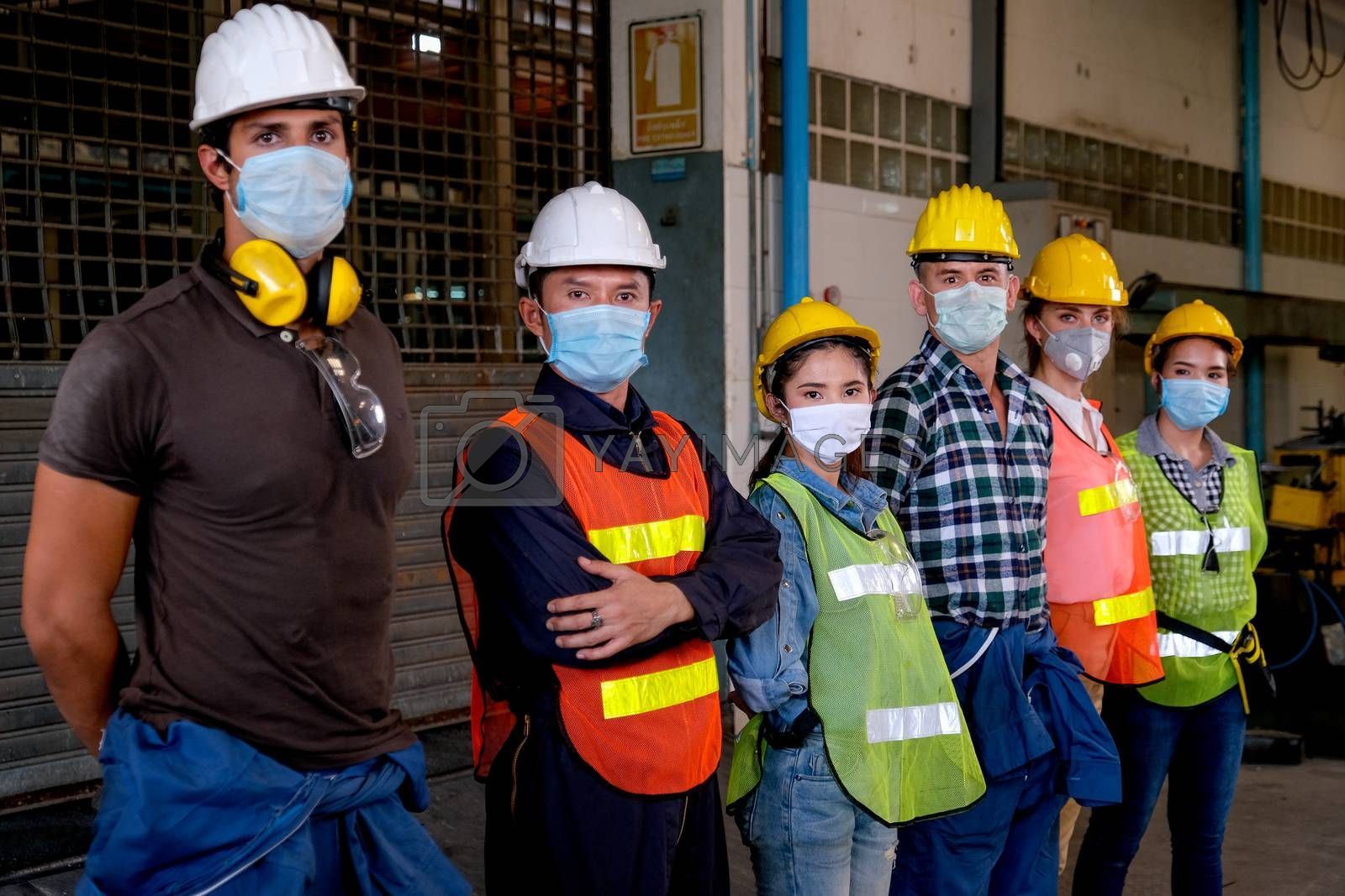 Group of workers or technician with mask stand and look right side direction and stay in factory area.
