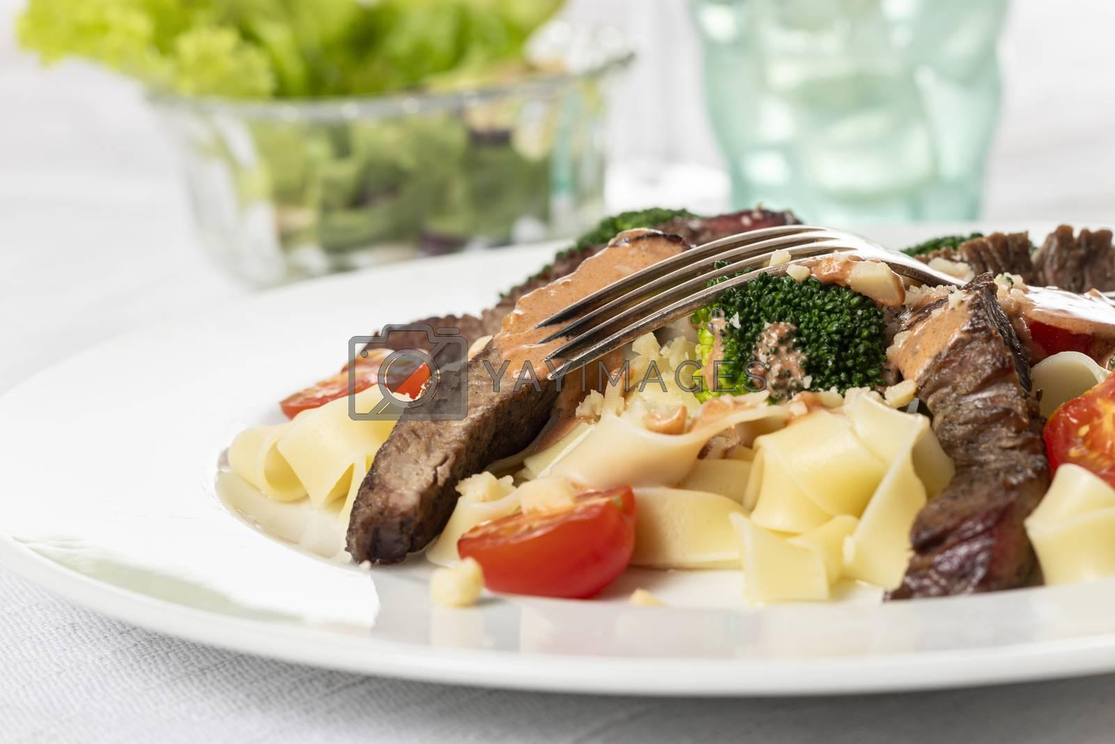 tagliatelli with steak slices on a plate