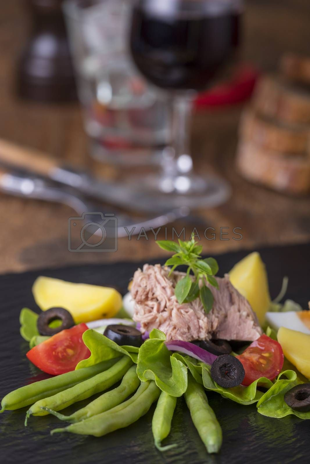salad nicoise on a wooden background