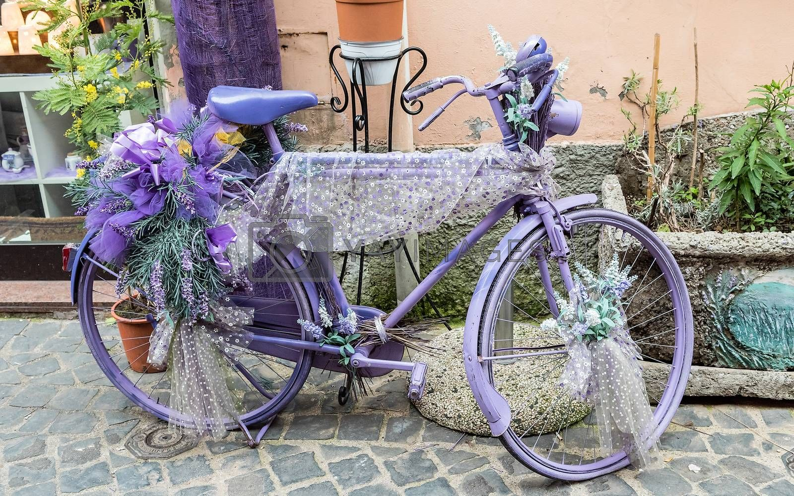Vintage violet bicycle decorated with flowers and laces
