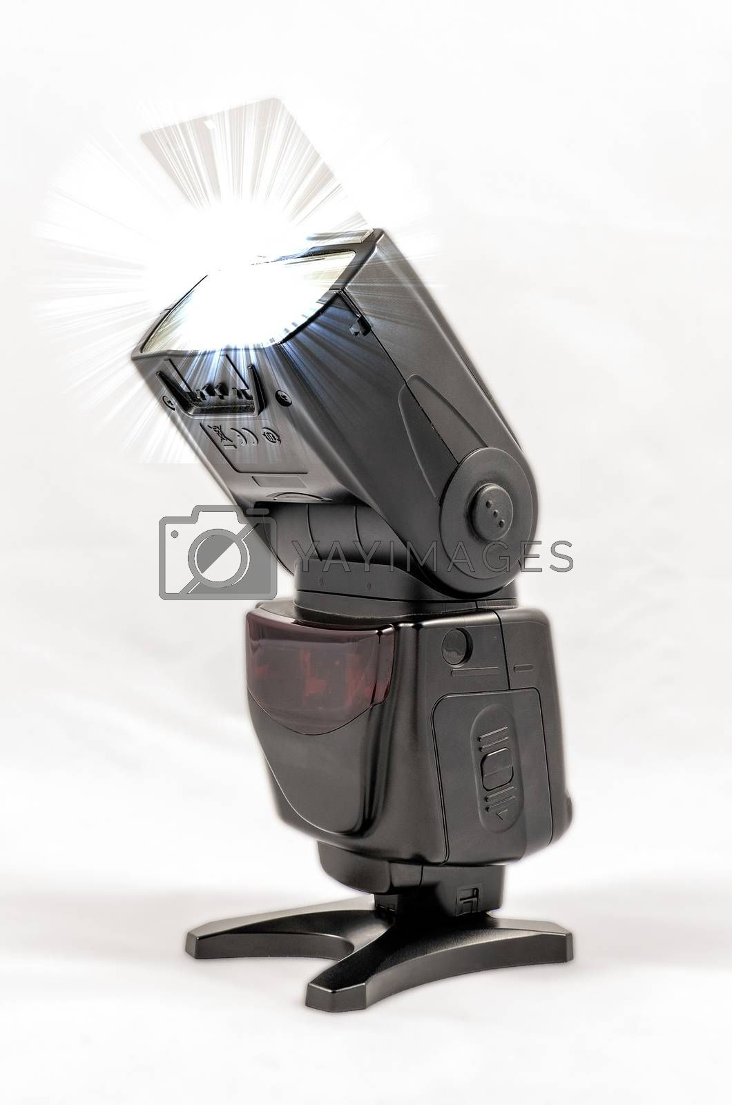 Oblique view of a black unbranded external flash unit for DSLR camera with bounce card extended while shooting