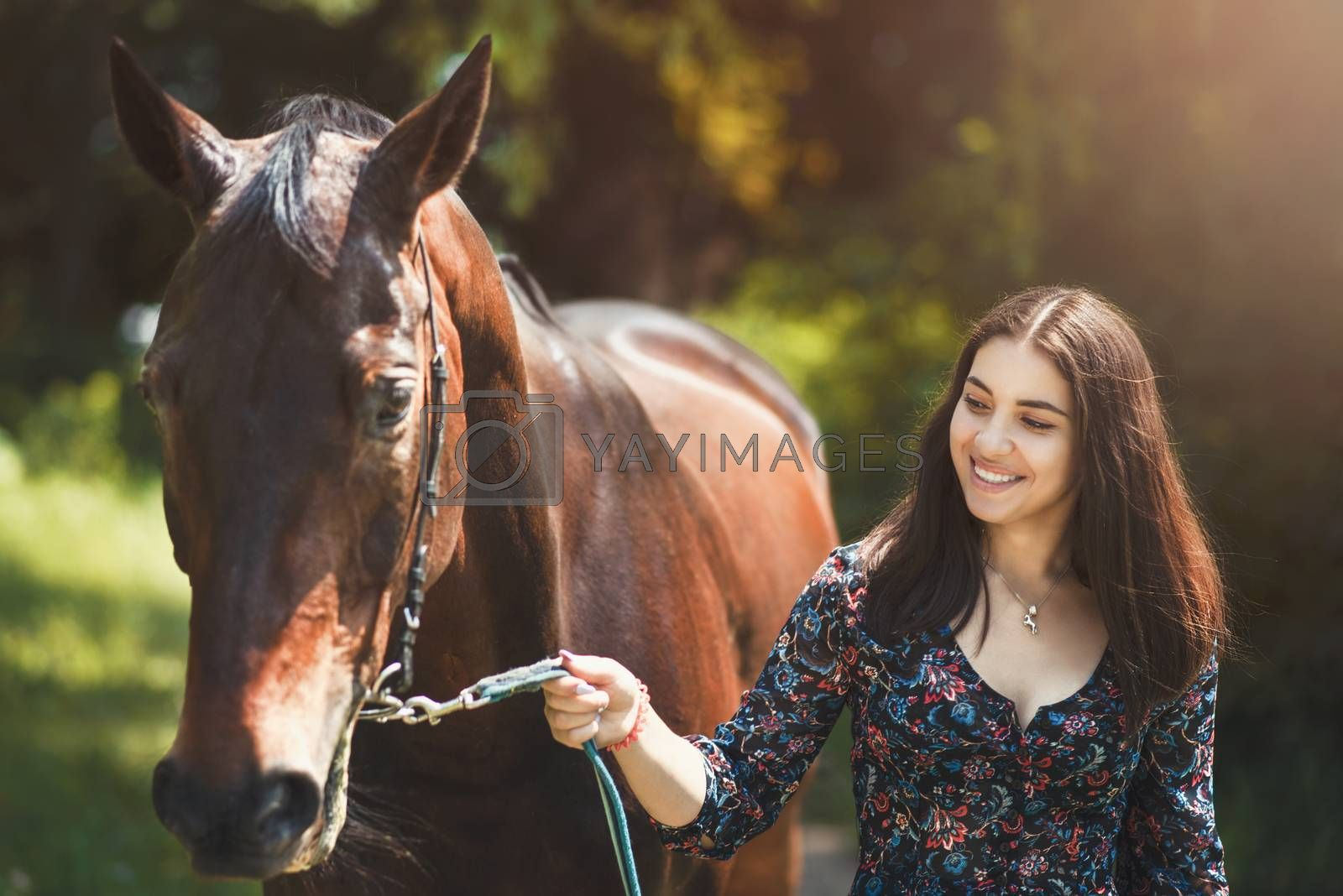 Beautiful Latin woman and her lovely horse walk in the forest. love animals concept