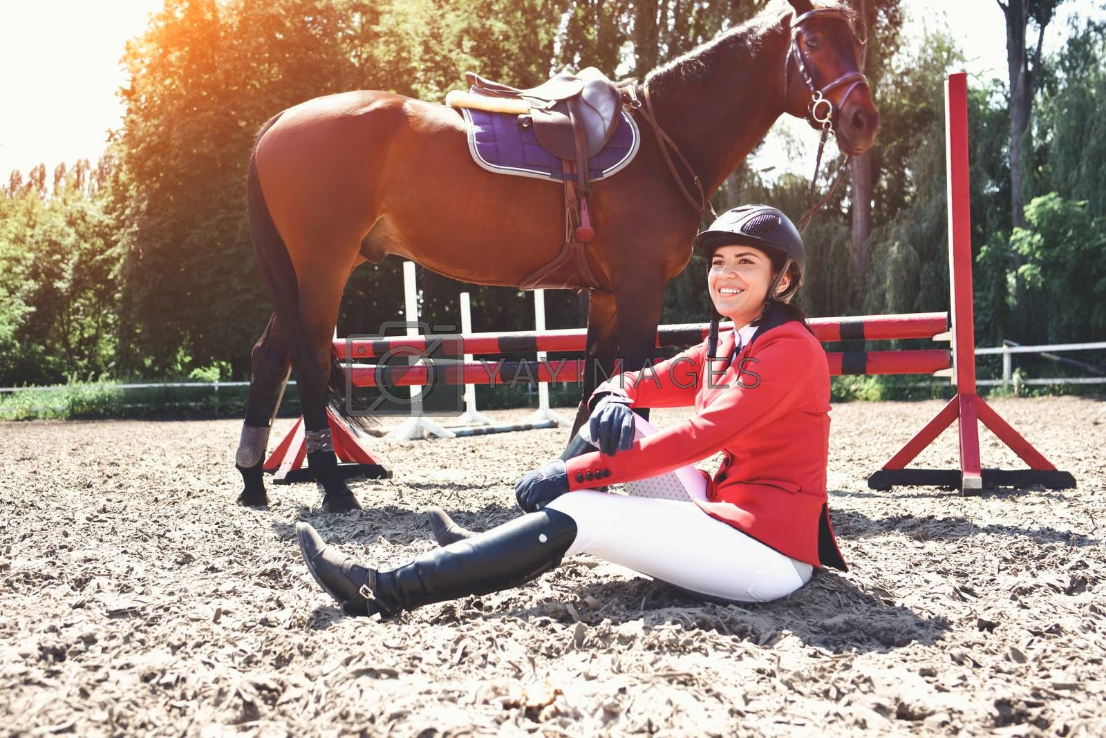young jockey and her horse posing after training. She loves the animals and joyfully spends her time in their environment.