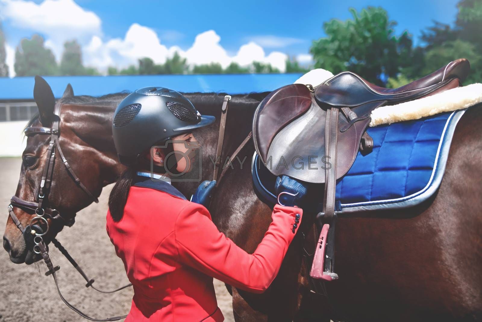 Girl jockey adjusts saddle on her horse to take part in horse races