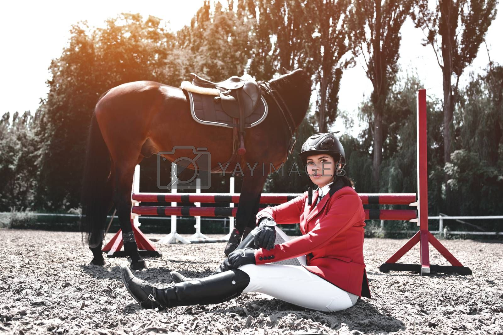 young jockey Girl and her horse posing after training. She loves the animals and joyfully spends her time in their environment.