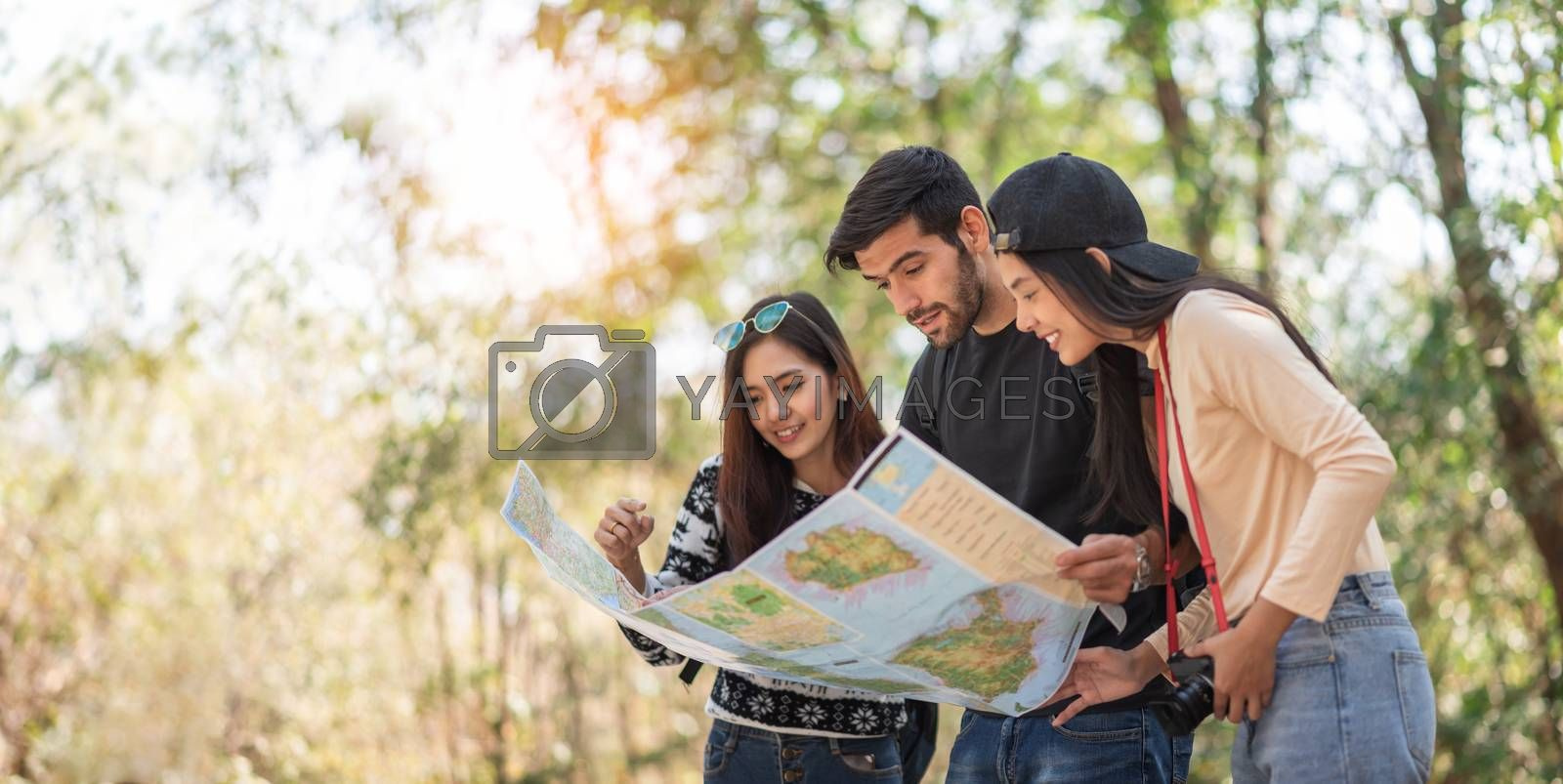 Multi-Ethnic Travelers looking at the map on travel vacations with natural background. Diversity, Friendship, People. copy space;