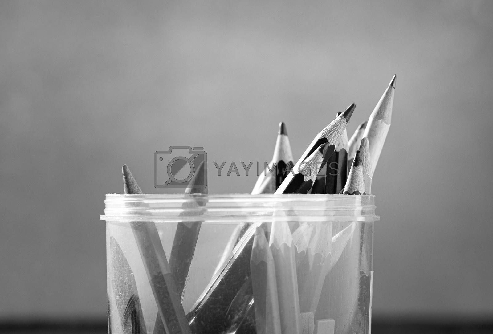Close up of Colored pencils are in a plastic round box placed on a wooden table by the window. Black and white style tone.