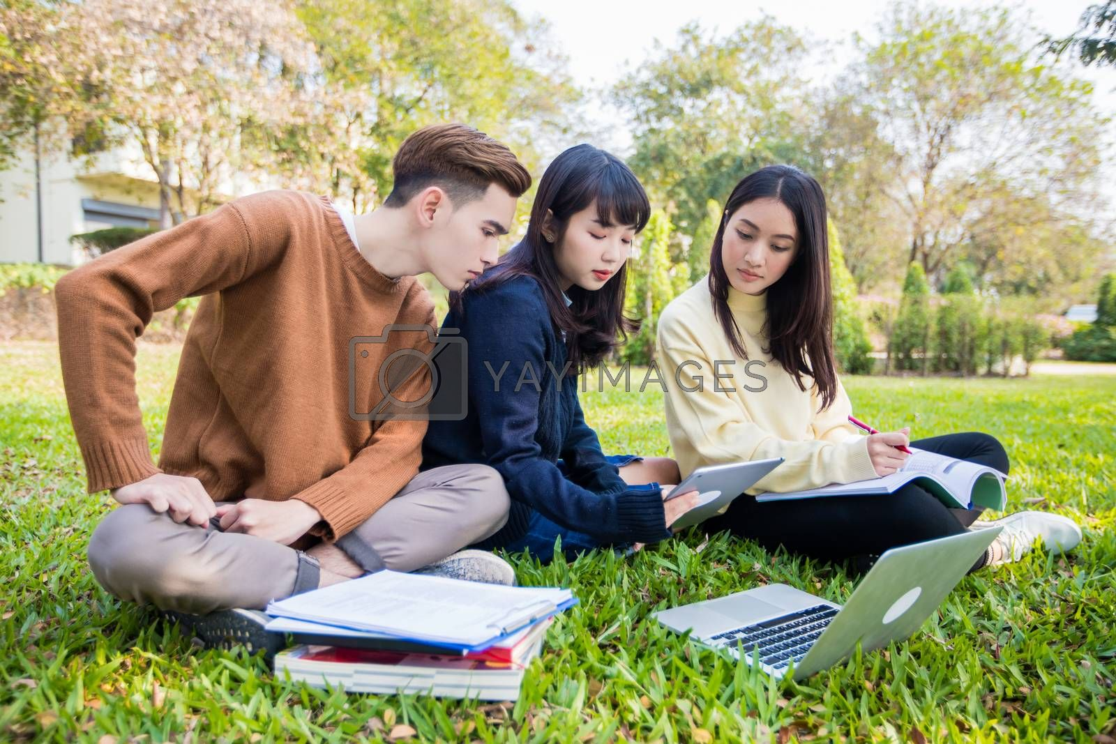 Asian students use notebook computers and tablet to work and study online in garden at home during the coronavirus epidemic and quarantine at home