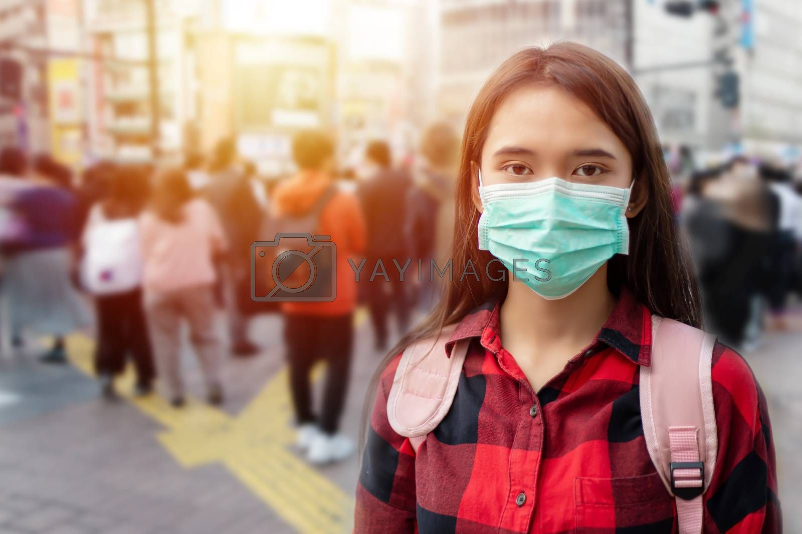 Asian Young woman walking in the city wearing protection mask on face because of air pollution, particulates and for protection flu virus, influenza, coronavirus