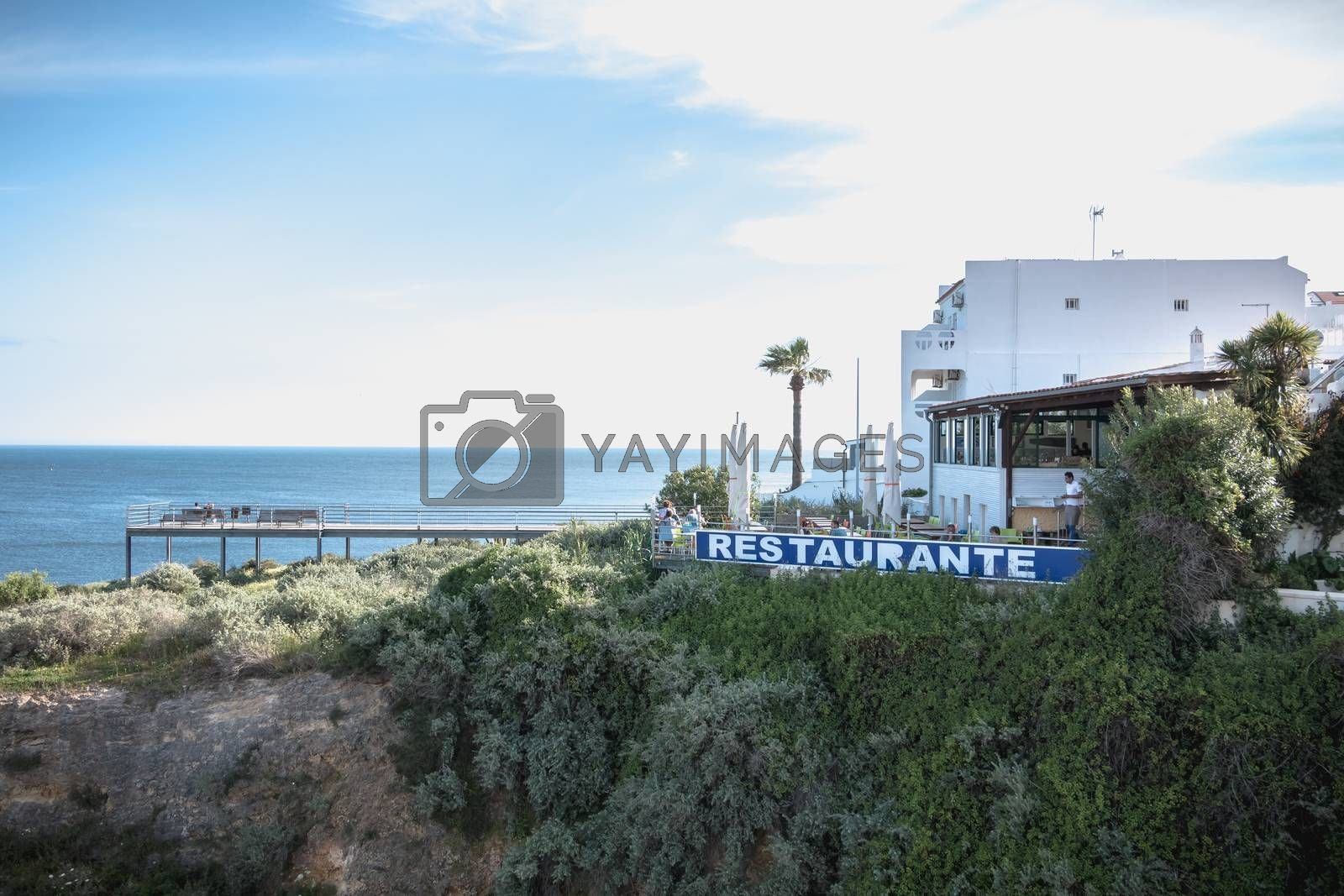 Albufeira, Portugal - May 3, 2018: People enjoying the sea view from the pontoon of a restaurant overlooking the beaches on a spring day