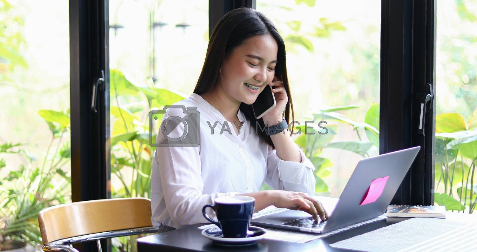 Asian Business women are using mobile and touch smart phone for Communication and women using notebook for working in coffee shop