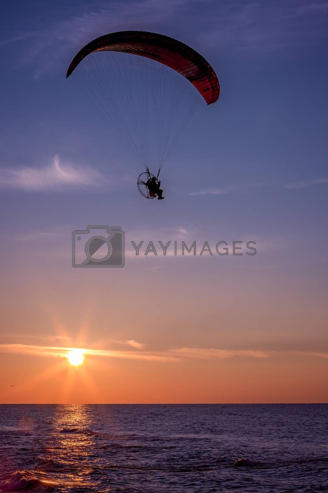 Paraglider flying with a paramotor during beautiful sunset