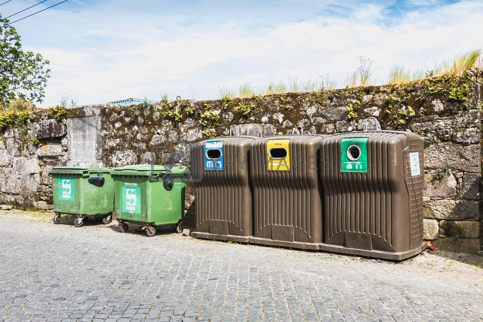 Vila Cha near Esposende, Portugal - May 9, 2018: Public recycling bins in front of a stone wall in the city center on a spring day