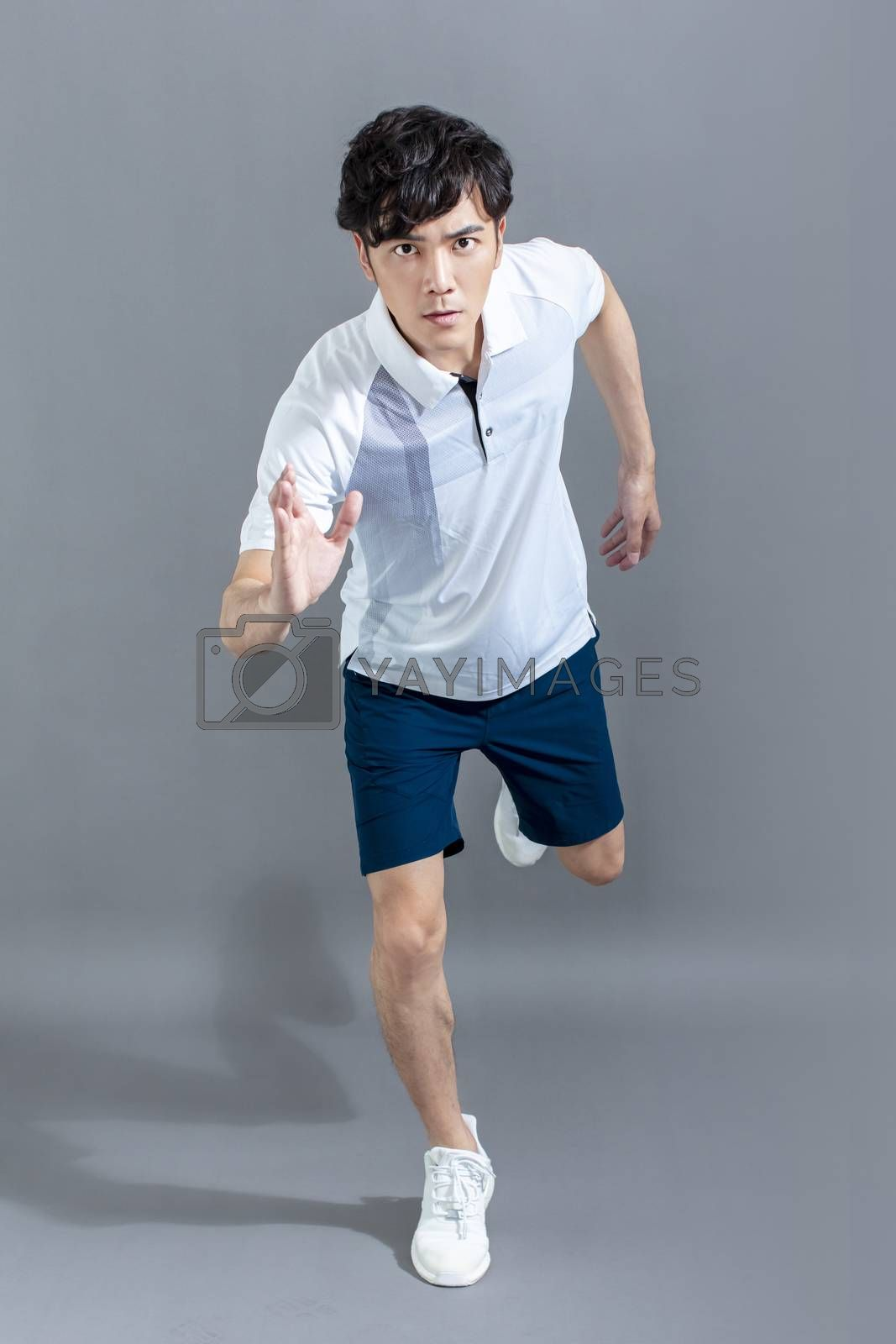 portrait of  fitness young man running on the gray background by tomwang