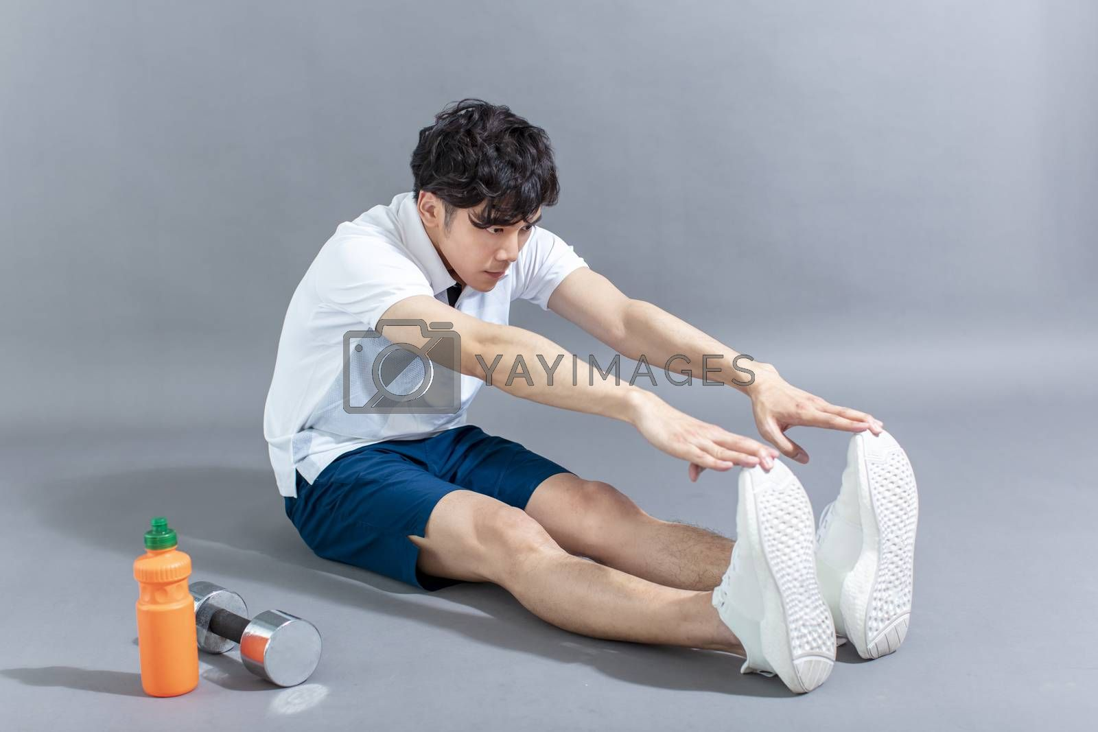 young man runner doing stretching exercise by tomwang