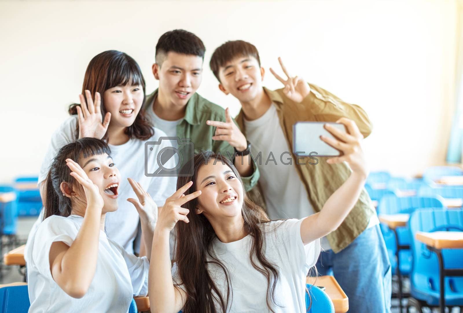 happy young group of teenagers making fun selfie in classroom