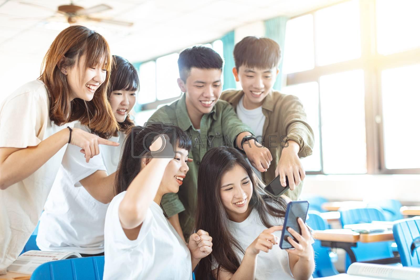 happy students looking at smartphones  in classroom
