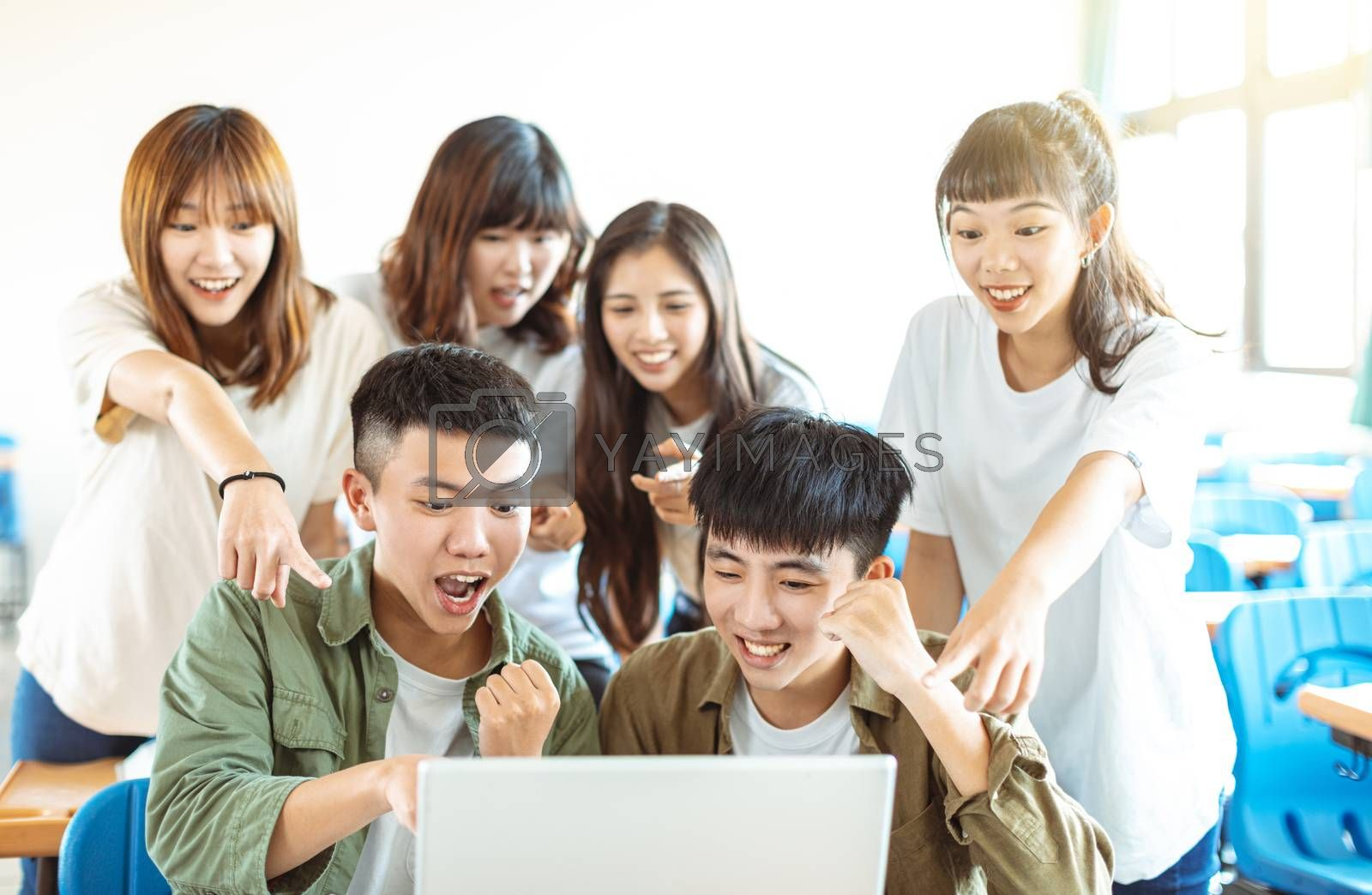 happy students looking at laptop  in classroom