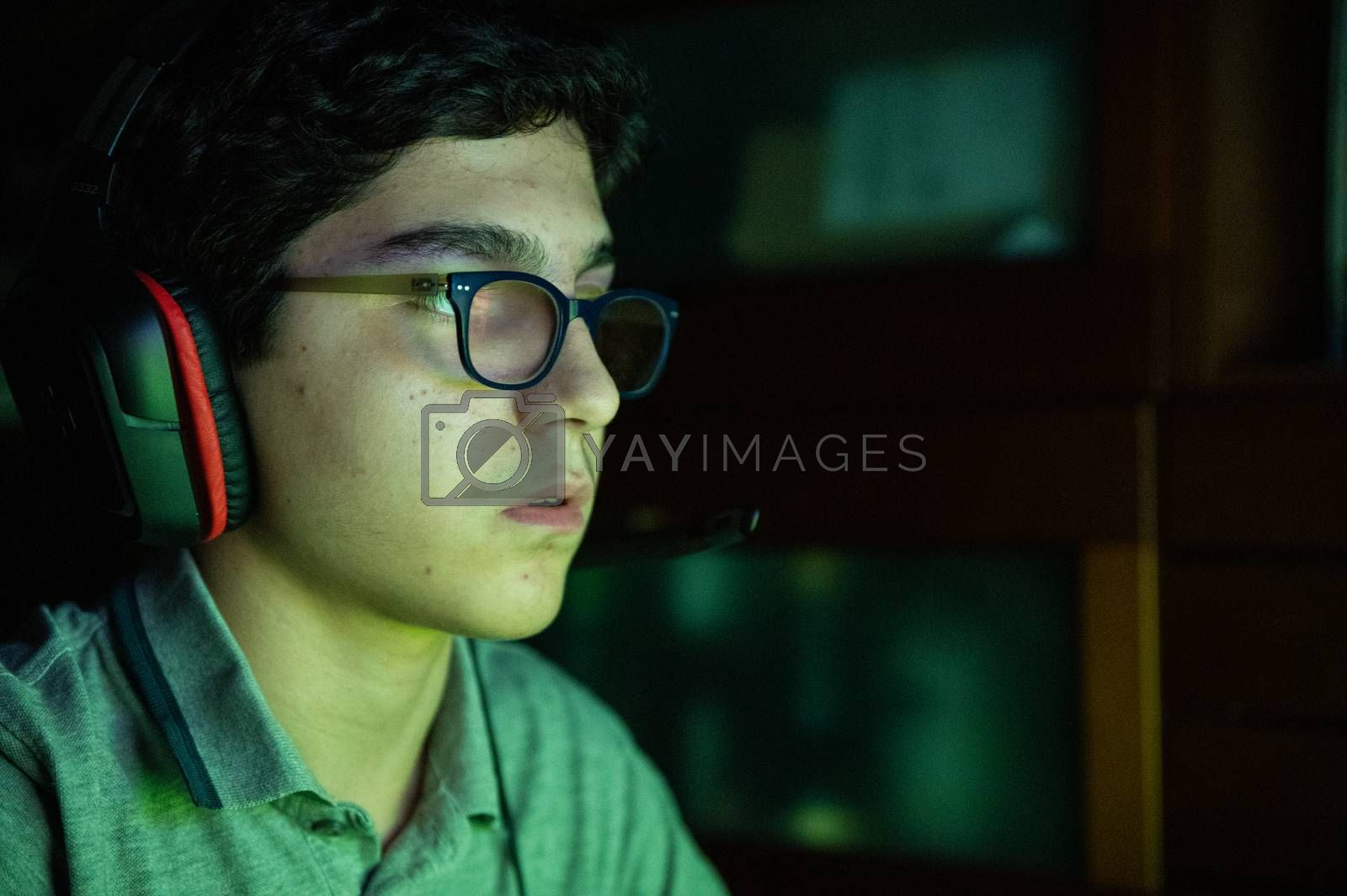 Game action during a video gaming session. The Caucasian boy with wavy black hair and glasses has his face illuminated by the changing colors of the screen during the game. Wear gaming headphones.