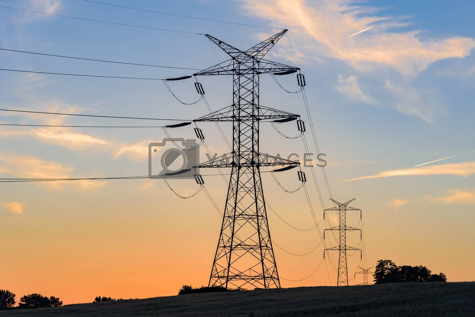 Electricity pylons and high voltage power lines at sunset