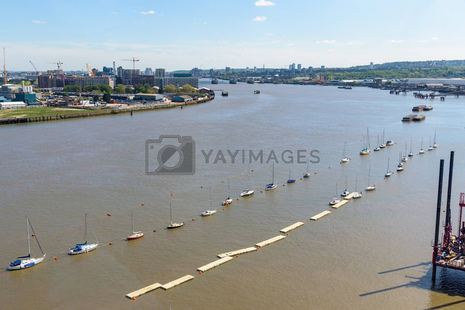 Aerial view of River Thames in eastern London with Thames Barrier in the background