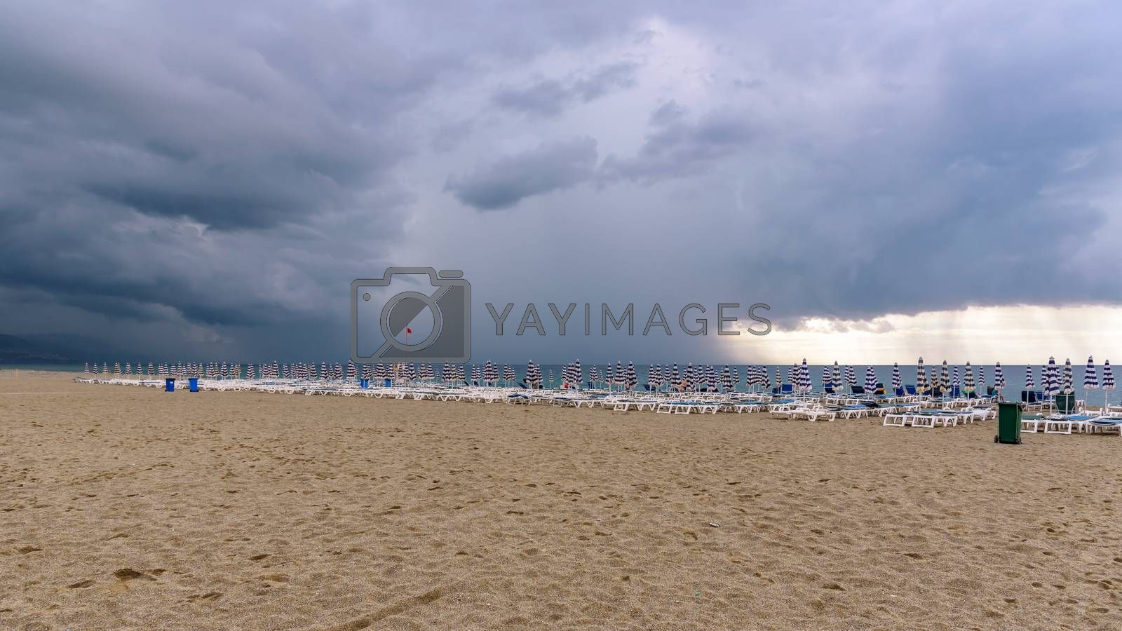 Sunbeds and umbrellas on the calabrian beach before the storm