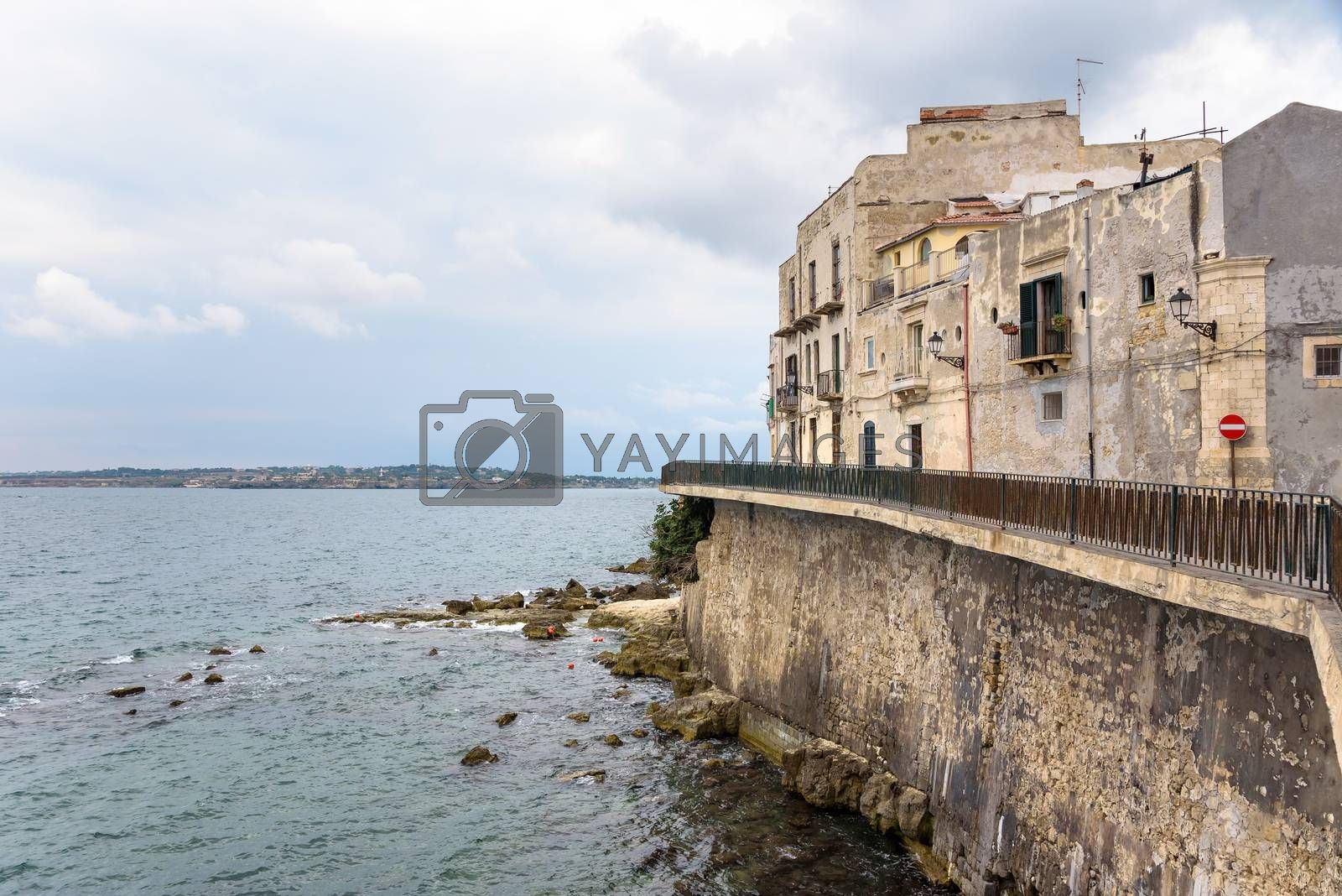 Waterfront with small pebble beach on Ortygia Island in Syracuse, Sicily, Italy