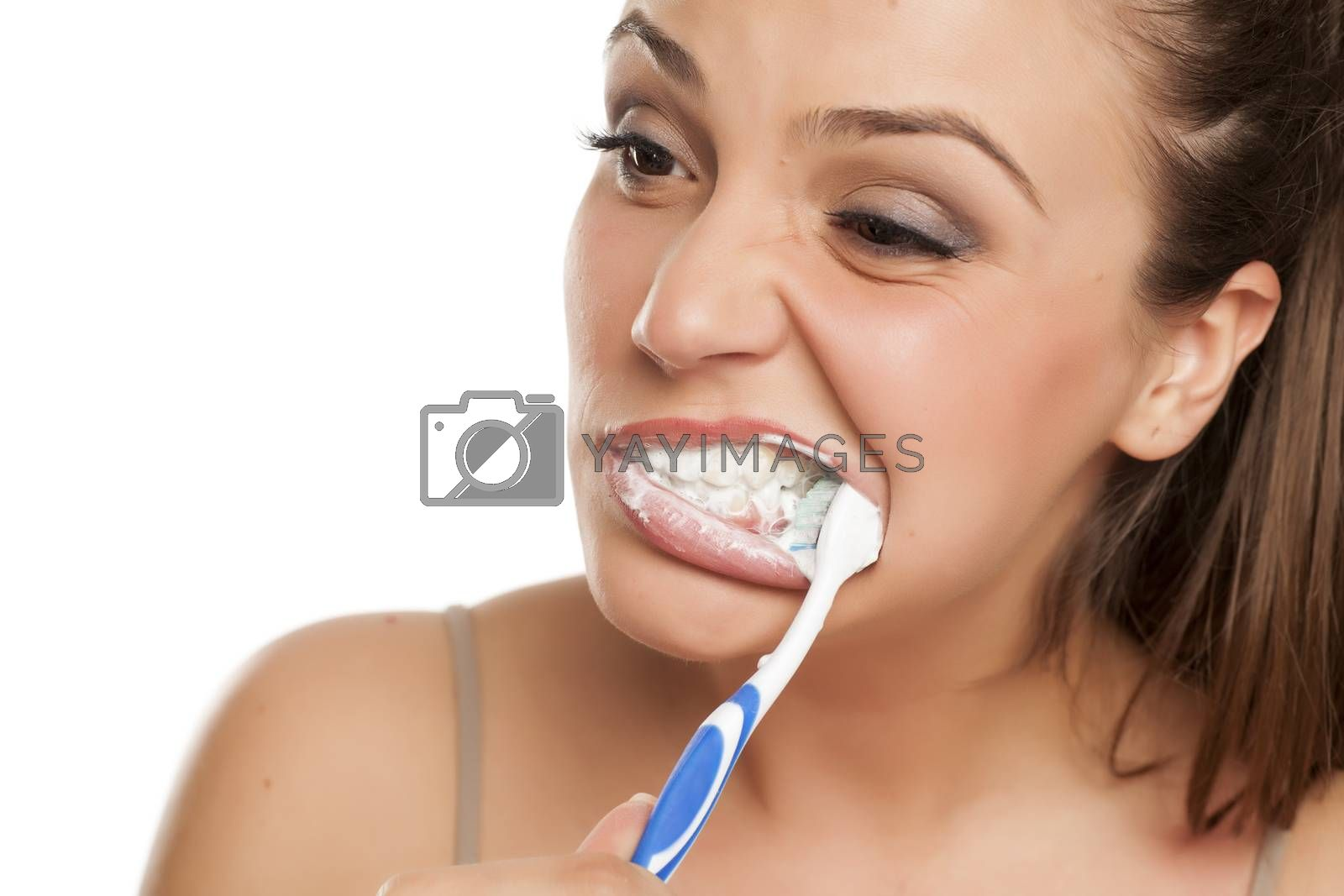 young happy woman brushing roughly her teeth on white background