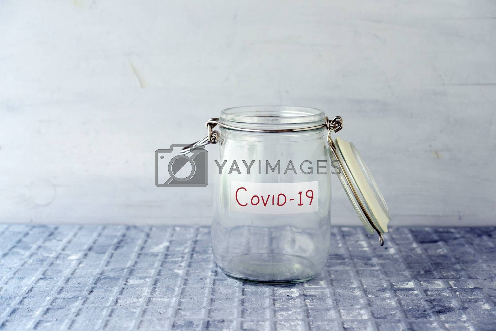 Empty glass money jar with covid19 label, financial concept.