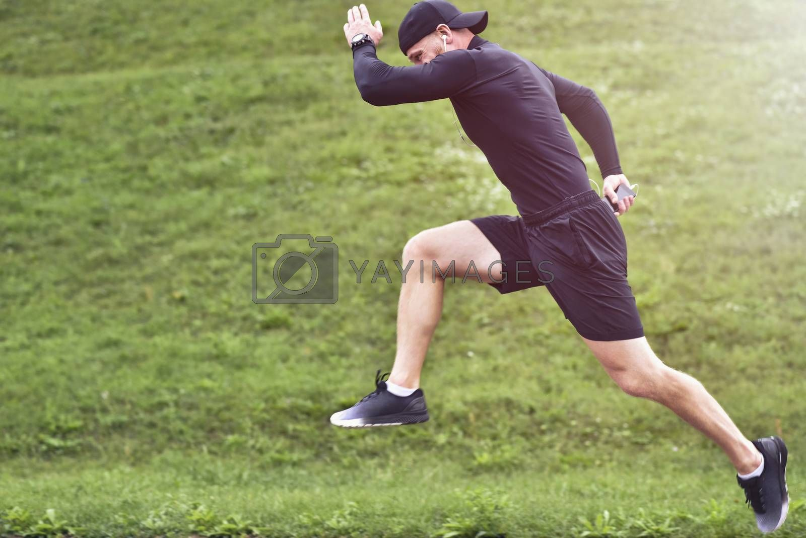 Portrait of concentrated confident muscular full of strength sportsman wearing shorts and sneakers.