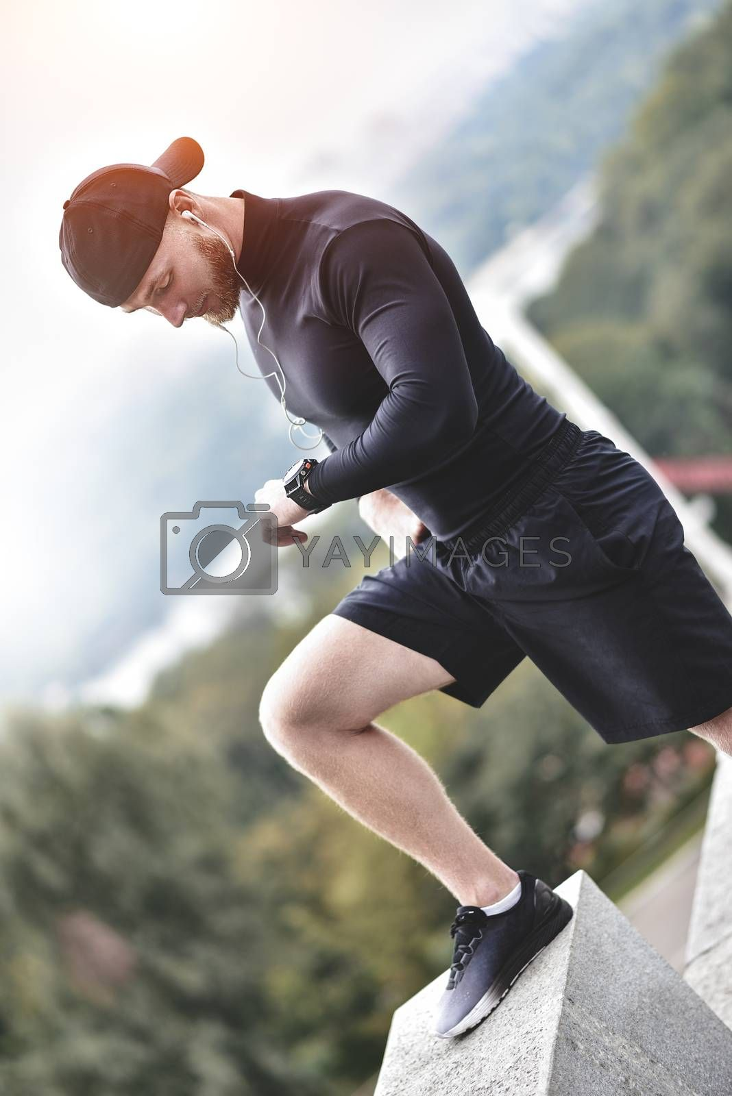 Muscular bearded athlete checking burned calories on smart watch after good workout session on city park.