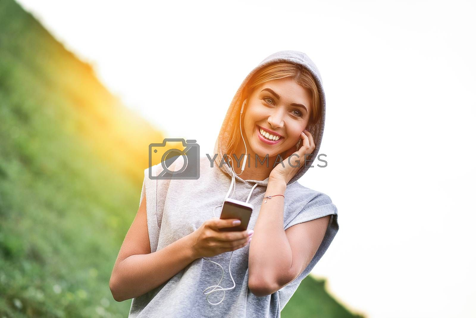 Beautiful young woman with headphones glad after nice jogging in city park