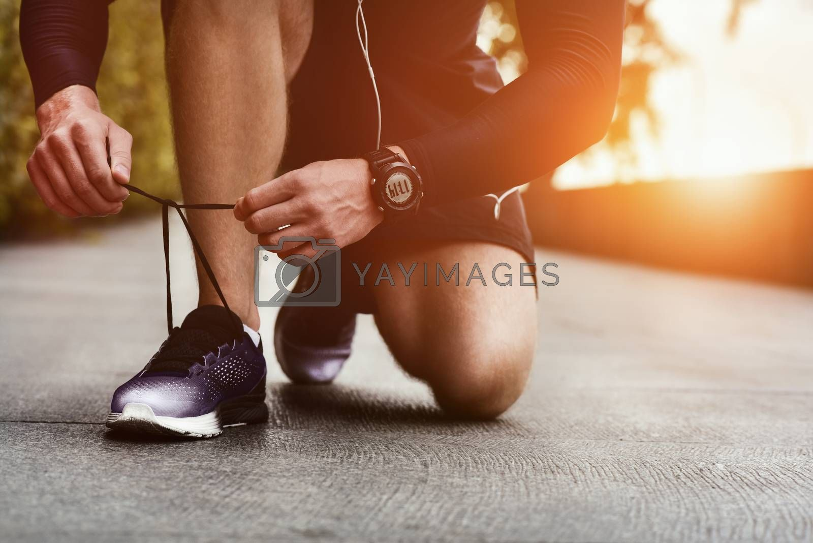 Cropped image of hands tying shoelaces on sneaker, running surface background. Hands of sportsman with pedometer tying shoelaces on sporty sneaker. Running equipment concept. Shoelaces tying by male hands.