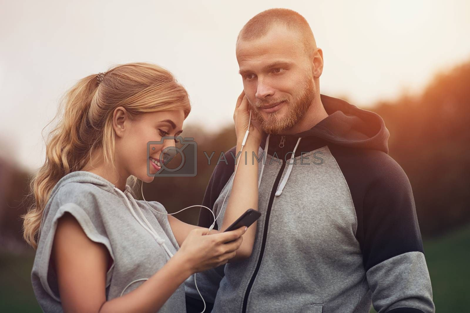 Caucasian sportive couple dating on after training, listening to music, having fun together. Sports and Outdoor Activities, Technology and People Relations Concept