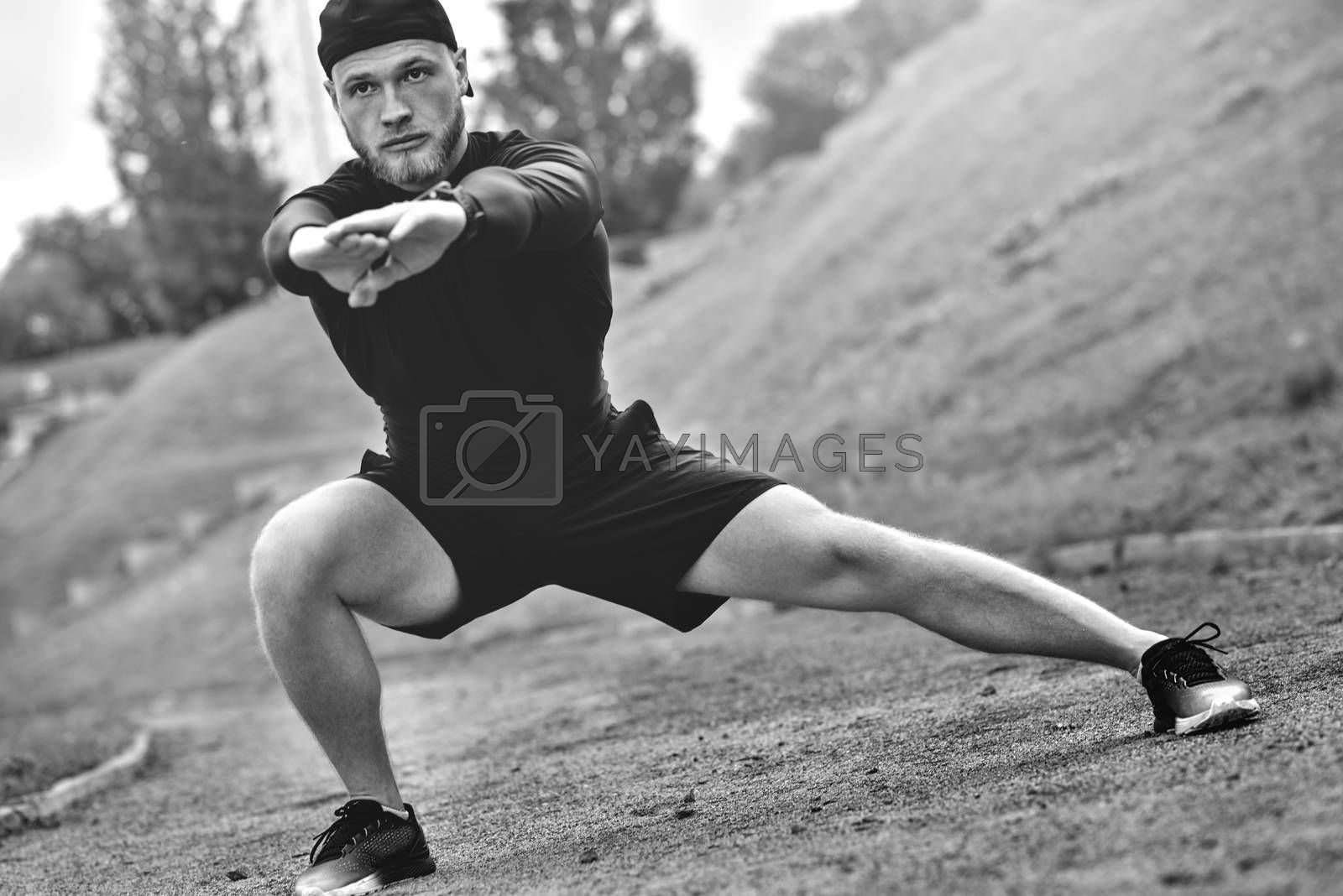 Muscular sportsman stretching out before a sports training at the street in city park