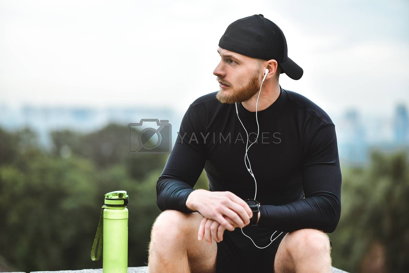 Muscular bearded athlete checking burned calories on smart watch after good workout session on city