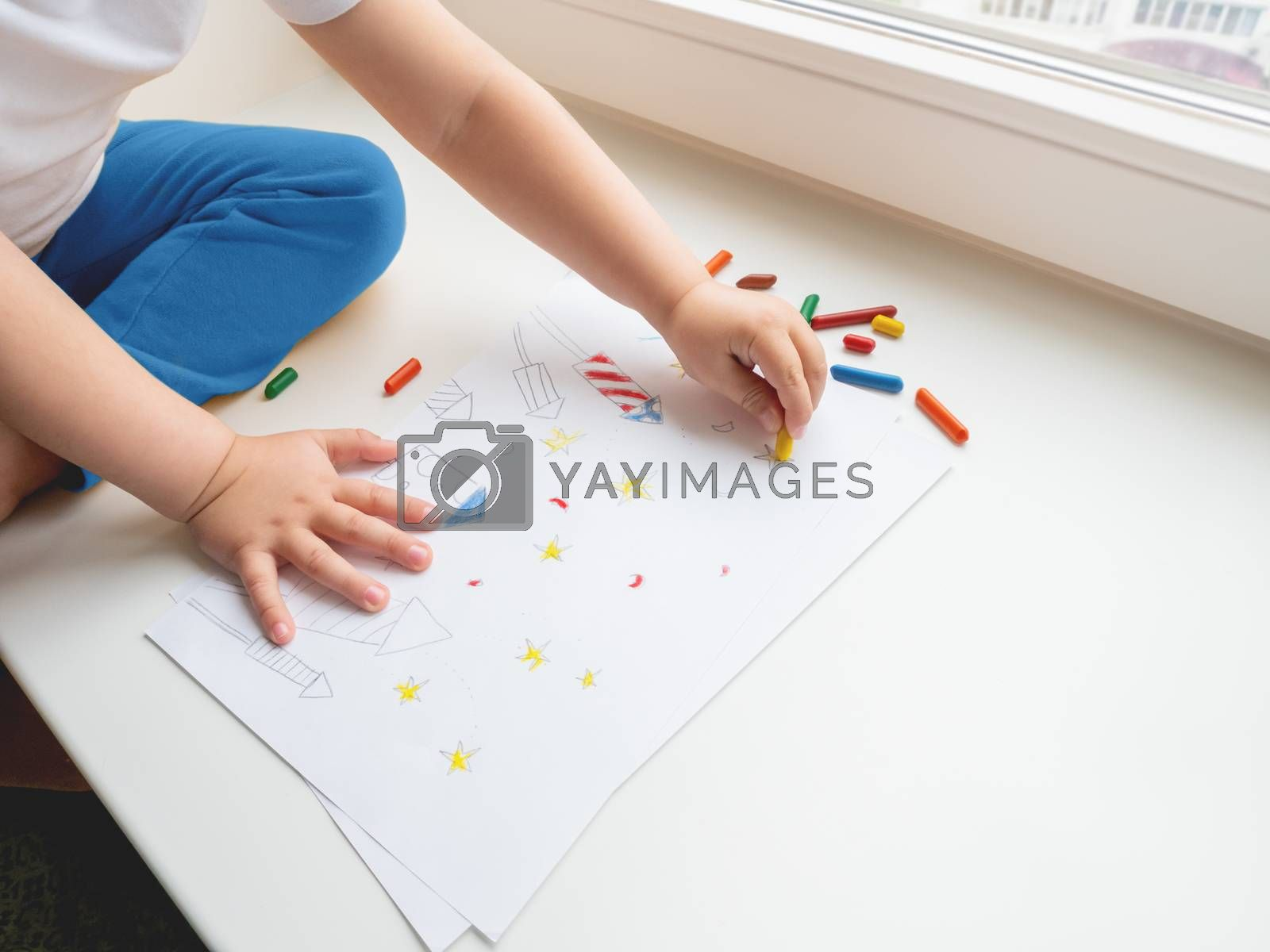 Toddler sits on windowsill and paints colorful fireworks. Child's picture to 4th of July celebration. Independence Day of USA symbol.