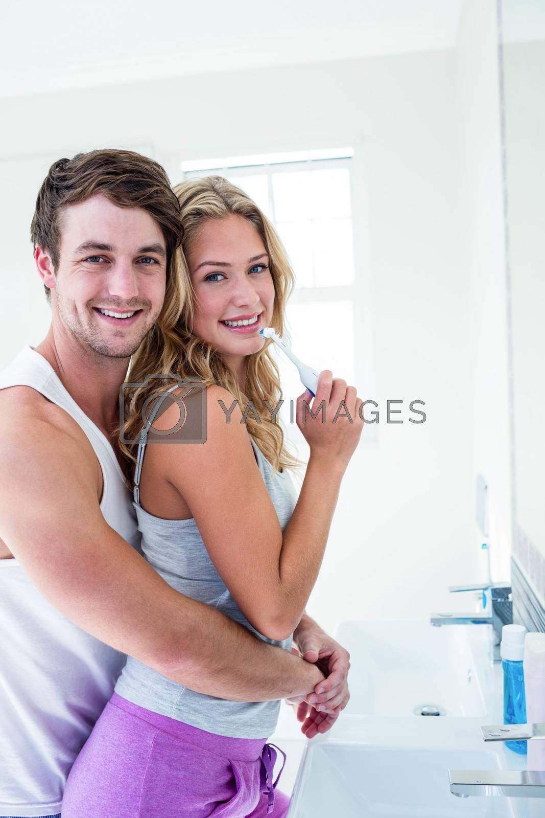 Young couple brushing their teeth at home in the bathroom
