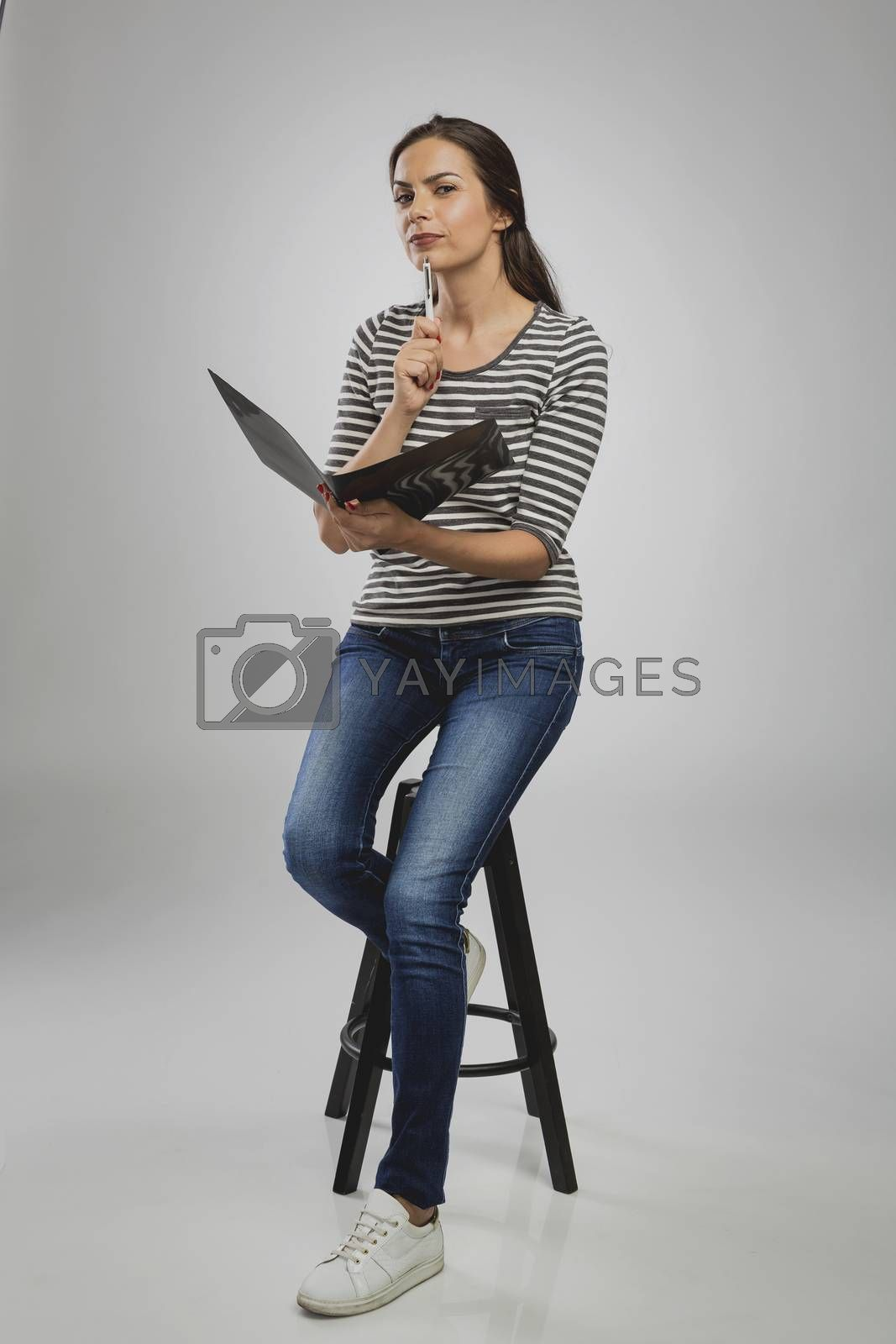 Beautiful woman sitting on a bench holding a folder and thinking        Woman sitting on a bench while think